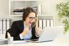 Noticias en línea de lectura emocionadas del oficinista en un ordenador portátil fotos de archivo