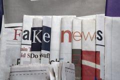 Noticias falsas en fondo de los periódicos fotografía de archivo
