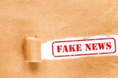 NOTICIAS FALSAS escritas debajo del papel rasgado Foto de archivo