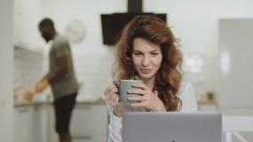 Noticias felices de lectura sonrientes de la mujer blanca en el ordenador portátil en cocina de la mañana almacen de metraje de vídeo