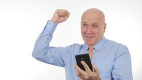 Noticias financieras de Gesticulate Happy Reading del hombre de negocios buenas en móvil fotografía de archivo libre de regalías