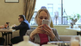 Noticias jovenes de la lectura de la empresaria con el smartphone, funcionamiento en el café, sonriendo almacen de video