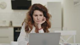 Noticias serias de la lectura de la mujer en el ordenador portátil en la cocina abierta Té de consumición de la señora joven almacen de metraje de vídeo
