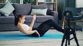 Notierendes Video des Sitzmädchens für das on-line-Blog, das ABS spricht auf Yogamatte dann, ausübend stock footage