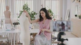 Notierendes Videoblog schöner Brunete-Damenschneiderin über tatsächliche Tendenzen der modernen Modeart r stock footage