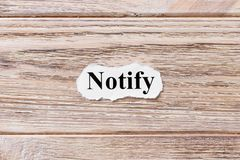 Notify of the word on paper. concept. Words of notify on a wooden background.  Stock Image