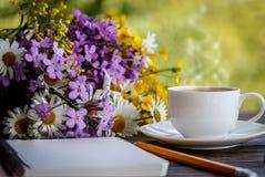 Notitieboekje, bloemen en kop van koffie op het bureau Royalty-vrije Stock Fotografie
