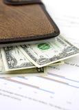 Notitieboekje en dollars op grafiek Stock Foto