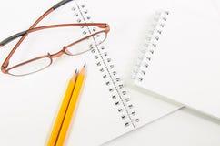 Notitieboekje en geel potlood en oogglas Stock Fotografie