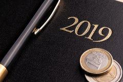 Notitieboekje en geld op de lijst Blocnote en euro bankbiljetten Het concept bedrijfs planning, reis, huisuitgaven stock foto's
