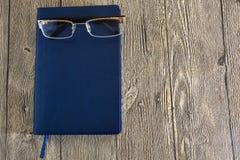 Notitieboekje en glazen Stock Fotografie