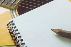 Notitieboekje en houten potlood op gitaar Royalty-vrije Stock Afbeelding