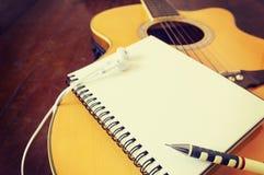 Notitieboekje en houten potlood op gitaar Stock Foto