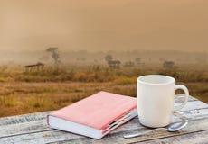 Notitieboekje en koffiekop op houten lijst met onduidelijk beeldachtergrond Royalty-vrije Stock Afbeelding
