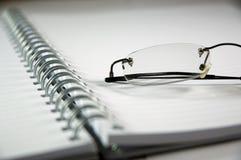 Notitieboekje en oogglazen Stock Foto