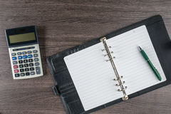 Notitieboekje en pen met calculator op het bureau Stock Foto