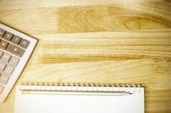 Notitieboekje en potlood met calculator op het bureau Stock Afbeeldingen