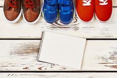Notitieboekje en tennisschoenen op hout Royalty-vrije Stock Foto