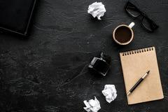 Notitieboekje, inkt, onderdompelingspen, koffie, glazen voor schrijverswerkplaats op donker bureau achtergrond hoogste meningsmod Stock Foto
