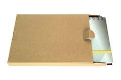 Notitieboekje in kartondoos die op een witte rug wordt geïsoleerdi Stock Fotografie
