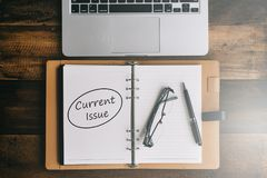 Notitieboekje, laptop, pen en bril op een houten lijst met HUIDIG KWESTIESwoord royalty-vrije stock afbeeldingen