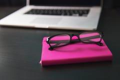 Notitieboekje, lezend glazen en laptop computer op zwart bureau Royalty-vrije Stock Foto's