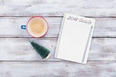 Notitieboekje met doelstellingen voor 2018 en kop van koffie op de houten mening van de lijstbovenkant Het concept van de plannin Stock Foto's