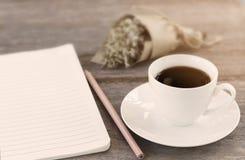 Notitieboekje met koffiekop en bloemboeket op witte lijst stock afbeelding