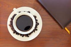 Notitieboekje met koffiekop op grungehout Stock Foto