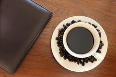 Notitieboekje met koffiekop op grungehout Royalty-vrije Stock Fotografie