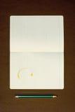 Notitieboekje met koffievlek en potlood op houten tafelblad Royalty-vrije Stock Afbeelding
