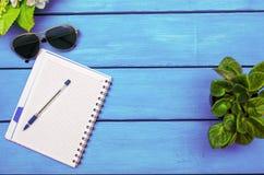 Notitieboekje met pen, bloemen, glazen op een blauwe houten achtergrond stock fotografie