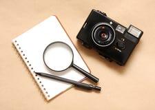 Notitieboekje met potlood en camera, het overdrijven Stock Fotografie
