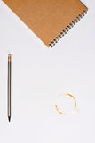 Notitieboekje met potlood en koffievlek op wit wordt geïsoleerd dat Royalty-vrije Stock Afbeeldingen