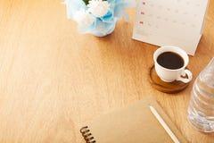 notitieboekje met potlood, koffiekop, kalender, flessenwater en bloem Stock Afbeelding