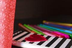 Notitieboekje met rood hart en een mand met kleurenpennen op draklijst en achtergrond stock afbeeldingen