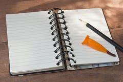 Notitieboekje met zwart potlood, verse oragebloem op houten lijst Stock Afbeeldingen