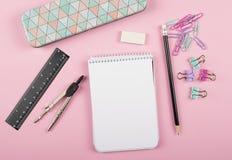 Notitieboekje naast kompas, klemmen, heerser en potlood op roze achtergrond stock afbeeldingen