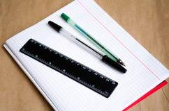 Notitieboekje o De levering van de school Pennen, potloden, een heerser, een schoon notitieboekje Witte lijst werkomgeving stock foto