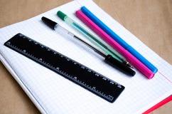 Notitieboekje o De levering van de school Pennen, potloden, een heerser, viltpennen en een schoon notitieboekje witte lijst stock foto