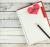 Notitieboekje open met de kaart van de valentijnskaartdag Stock Foto's