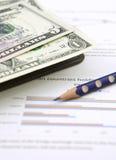 Notitieboekje, potlood en dollars op grafiek Stock Afbeeldingen