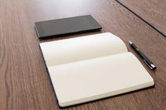 Notitieboekje, tablet en pen op een houten lijst Het werkruimte voor een jou stock fotografie