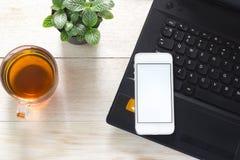 Notitieboekje, Telefoon en een kop thee op de lijst Kan geassembleerde advertentie zijn Stock Afbeelding