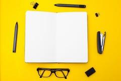 Notitieboekje voor ingangen en zwarte voorwerpen op een gele achtergrond M Stock Afbeelding