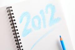Notitieboekje (writed 2012) en blauw potlood Stock Afbeeldingen