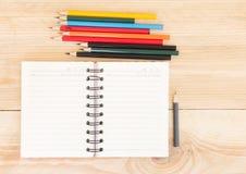 Notitieboekjedocument en school of bureauhulpmiddelen op houten lijst Stock Foto