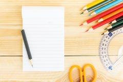 Notitieboekjedocument en school of bureauhulpmiddelen op houten lijst Stock Afbeeldingen