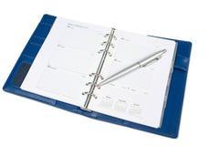 Notitieboekjekalender met zilveren die pen op witte achtergrond wordt geïsoleerd Royalty-vrije Stock Foto's