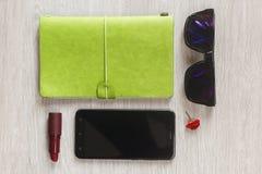 Notitieboekjeontwerper, mobiele telefoon en roze handtas van levensstijl werkende vrouw voor zaken bij bureau op witte houten als royalty-vrije stock fotografie